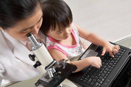 Mother busy working with microscope and her daughter busy playing laptop. focus mainly on little girl photo