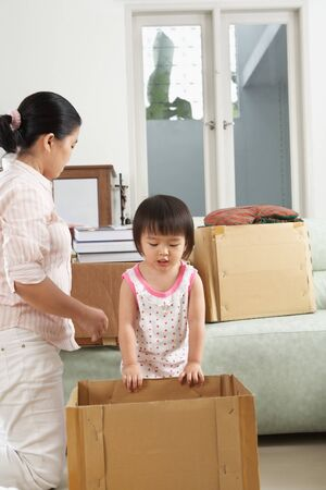 Mother and daugher packing items for moving house photo