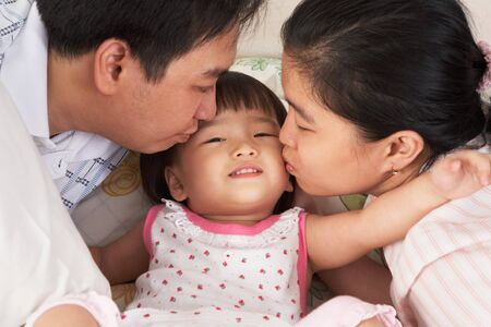 Parent kissing their beloved daughter on bed. photo