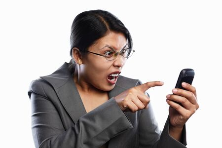 Asian businesswoman angry expression using video call of her cell phone feature, isolted on white background