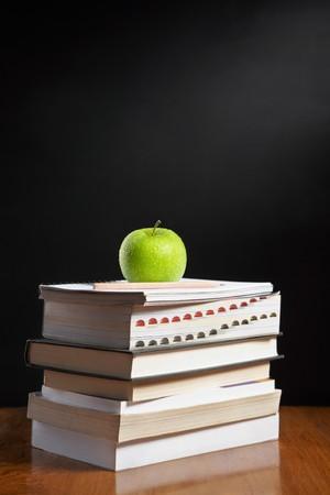 shool: Green apple over pile of books for shool concept Stock Photo
