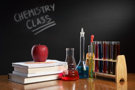 erlenmeyer: Chemistry class concept with red apple on pile of books and chemical solution