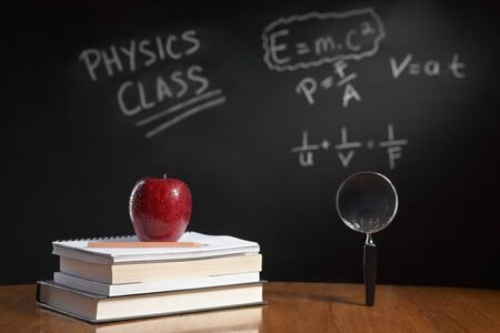 physics: Physics class concept with red apple on pile of books and magnifying glass with equation on blackboard