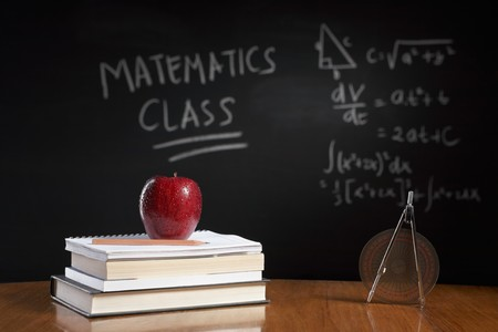 Mathematics class concept with red apple on pile of books and drawing compass with equation on blackboard photo