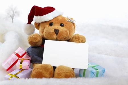 Christmas teddy bear doll holding blank paper