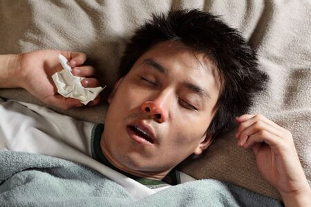 flu: A male Chinese man is sleeping while catching cold and breathing through mouth because of the flu