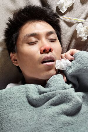An Asian sick man, sleeping with thermometer showing high temperature photo