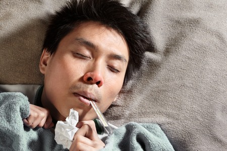 A sick male sleeping while themometer is in his mouth photo