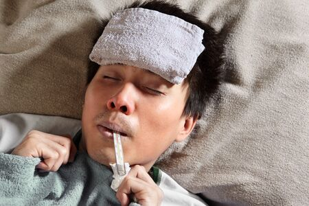 A sick male sleeping with wet towel on his forehead to reduce high high fever photo