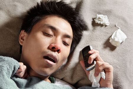 A sick man sleeping while holding his cell phone photo