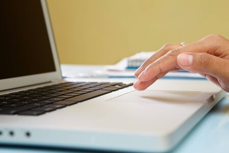 unrecognizable people: Hand using laptop in office, unrecognizable people