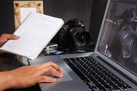 Photographer still working on the photos using laptop photo