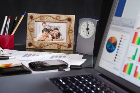 family picture: Office desk full of stuff: laptop, clock, document, family picture and other things. ****** The picture were my collection in my porfolios here ****** Stock Photo
