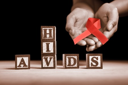 Hand holding red ribbon on back of HIV-AIDS letter blocks photo