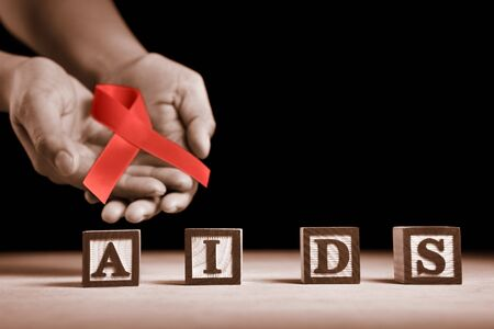 letter blocks: Hand holding red ribbon on back of AIDS letter blocks Stock Photo