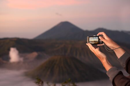 low light: People hand taking landscape picture in the early morning. *** noticable noise because low light condition *** Stock Photo