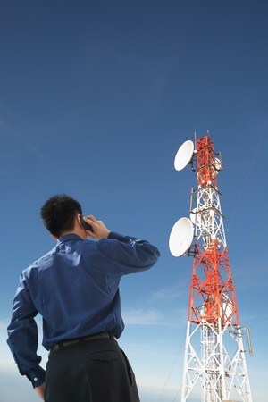 telecommunications equipment: Backside of  businessman on the  phone and antenna against blue sky Stock Photo