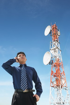 Chinese businessman on phone and antenna against blue sky photo