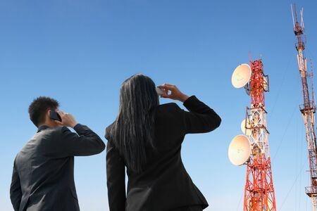 telecommunication equipment: Backside of  business pople on the  phone and antenna against blue sky