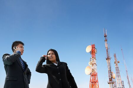 Asian business people on the phone and antenna against blue sky photo