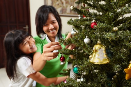 Asian mother and daughter decoarting Christmas tree in the living room ogether photo