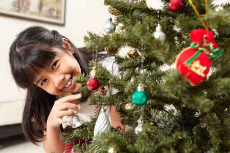 Smiling Asian little girl and Christmas tree at home photo