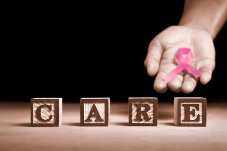Word 'Care' from wooden block with hand holding pink ribbon on dark background Stock Photo - 7988134