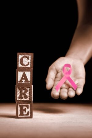 Word Care from wooden block with hand holding pink ribbon on dark background