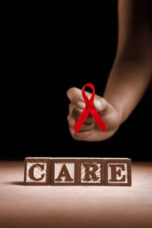 Word 'Care' from wooden block with hand holding red ribbon on dark background Stock Photo - 7988162