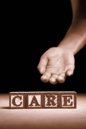 Word 'Care' from wooden block with hand gesture on background Stock Photo - 7988137