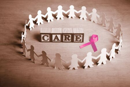 Pink ribbon with word 'Care' surrounded by female paperdoll Stock Photo - 7988340