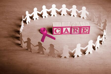 cancer ribbon: Pink ribbon with word Care surrounded by female paperdoll Stock Photo