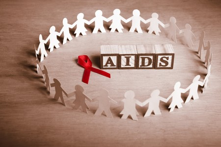 Red ribbon with word 'AIDS' surrounded by couple paperdolls Stock Photo - 7988339