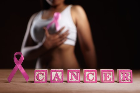Pink ribbon and pink word 'CANCER' in front of woman's body Stock Photo - 7988329