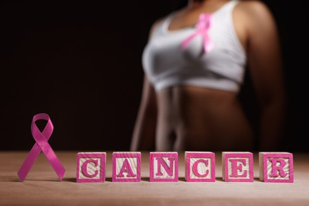 breasts: Pink ribbon and pink word CANCER in front of womans body Stock Photo