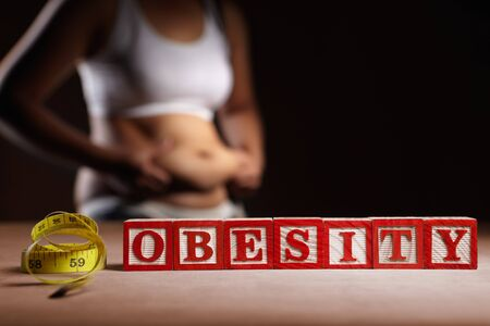 low fat: Word OBESITY with measruing tape in front of womans body holding her big belly Stock Photo