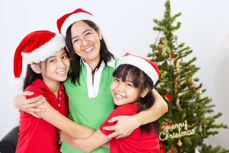 Asian mother and daughters on Christmas, hug each other photo