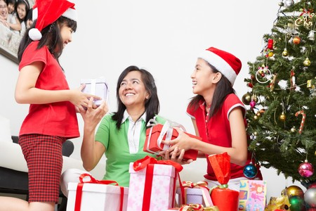 Mother and daughters exchanging present on Christmas photo