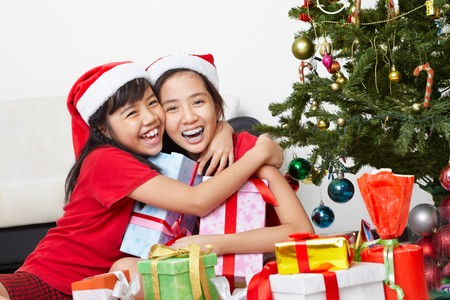 Tw little female siblings showing their love in Christmas season photo