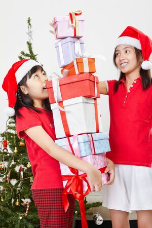 Two kids busy arranging pile of Christmas presents photo