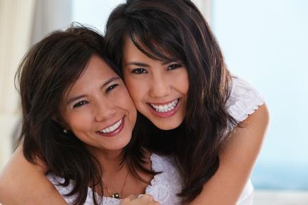 mama e hija: Feliz pose de madre e hija en su casa.  Foto de archivo