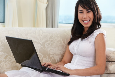 Young Asian female using laptop on sofa photo