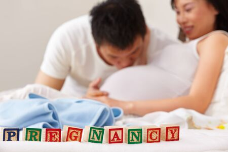 pregnant couple: Word pregnancy in front of happy couple, the husband kissing his pregnant wife stomach Stock Photo