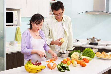 Asian couple ( pregnant wife ) busy preparing food in kitchen Standard-Bild