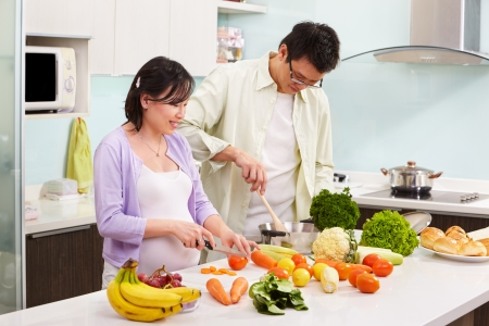 mujeres cocinando: Ocupado de preparar la comida en la cocina asi�tica par (esposa embarazada)
