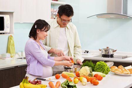 marido y mujer: Ocupado de preparar la comida en la cocina asi�tica par (esposa embarazada)