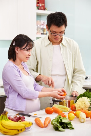Asian couple ( pregnant wife ) busy preparing food in kitchen photo