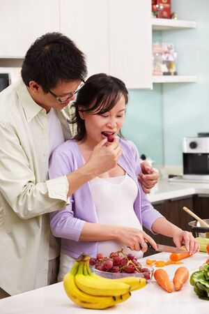 Asian couple activity in kitchen, with lots of fruit and vegeteable, where the couple eating fruit photo
