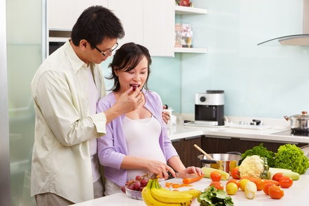 Asian couple activity in kitchen, with lots of fruit and vegeteable, where the couple eating fruit Stock Photo