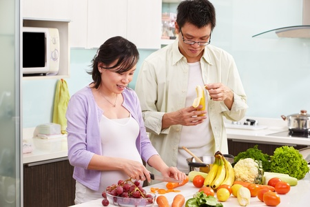 Asian couple activity in kitchen, with lots of fruit and vegeteable, where the couple eating fruit Standard-Bild